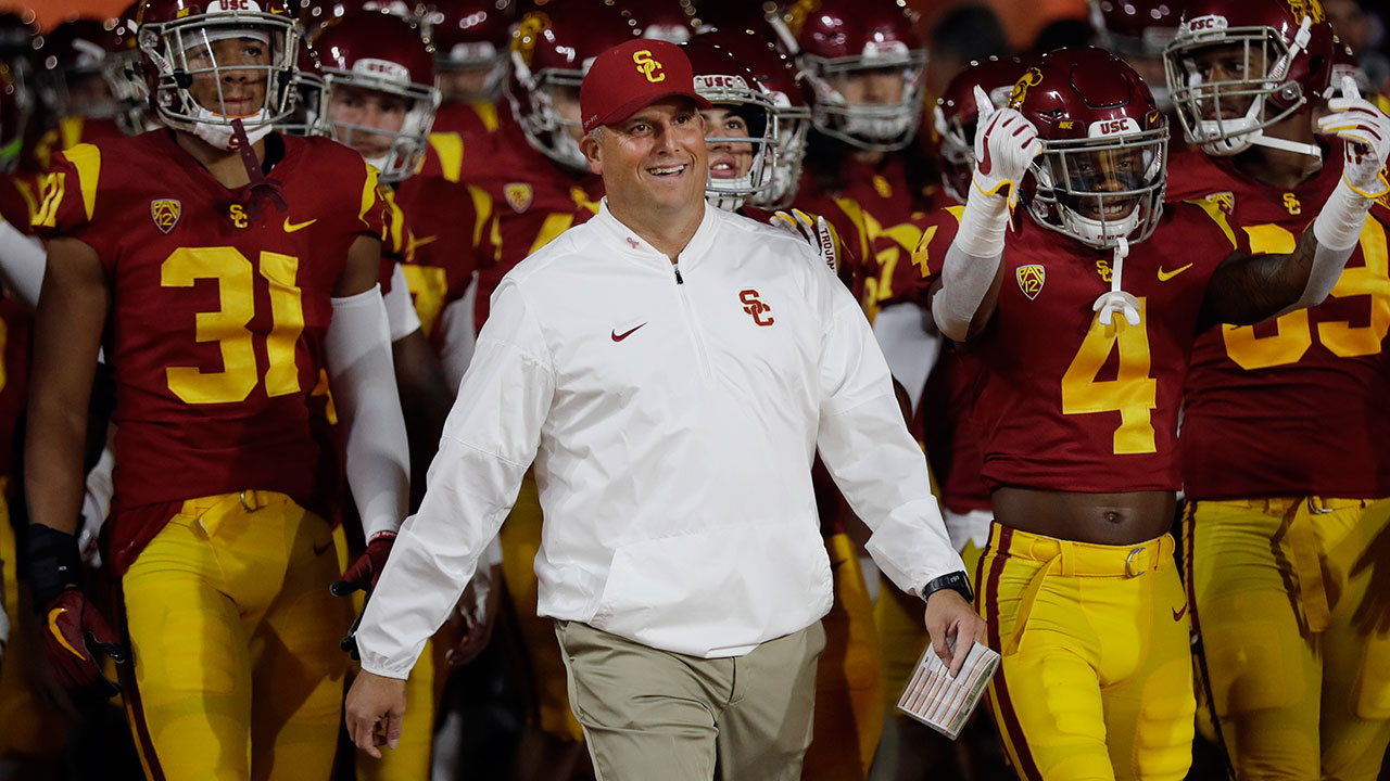 FILE - In this Oct. 13, 2018, file photo, USC head coach Clay Helton smiles as he enters the field with his team during an NCAA college football game against Colorado.