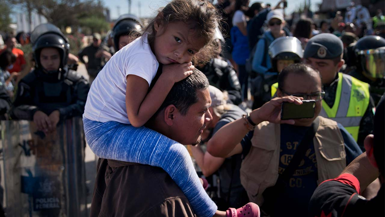 A young migrant sits on a mans shoulders as they join a group of migrants trying to push their way past the Chaparral border crossing in Tijuana, Mexico, Sunday, Nov. 25, 2018.