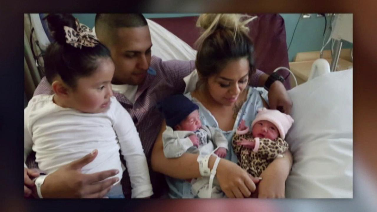 Proud parents hold their twin son and daughter who were born on different days in different years.
