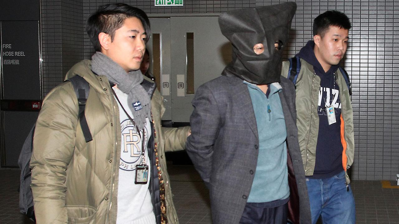 Deyun Shi, 44, center, is escorted by police officers while in custody in Hong Kong Sunday, Jan. 24, 2016.