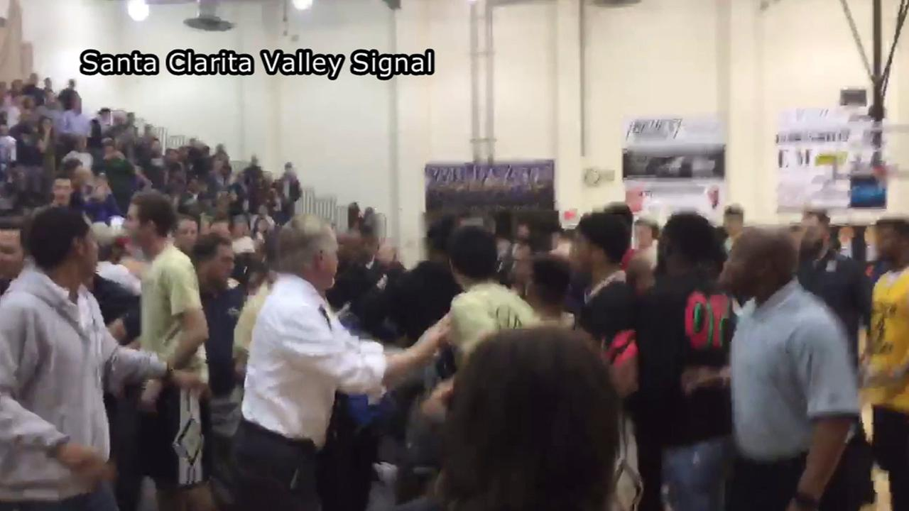 Basketball players and coaches swarm the court during a game Tuesday, Jan. 26, 2016 after a player from Golden Valley High School assaulted a student at West Ranch High School.