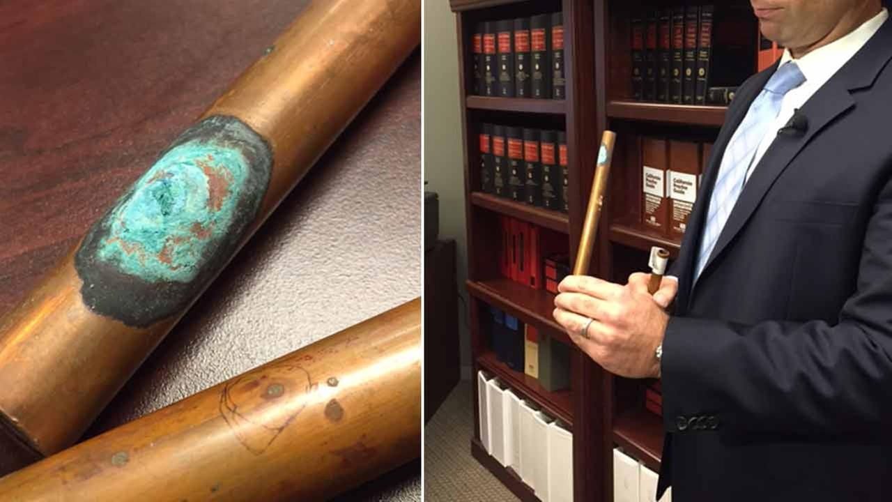 Copper pipes from an Orange County home with pitting that led to pinhole-sized leaks (left) and attorney Michael Artinian holding another copper pipe (right) in an undated photo.