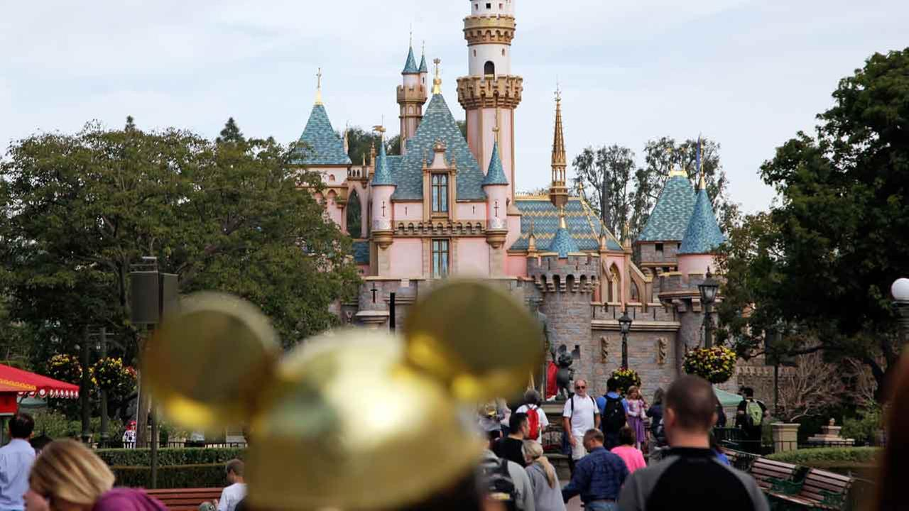 FILE - In this Jan. 22, 2015 file photo, visitors walk toward the Sleeping Beautys Castle in the background at Disneyland Resprt in Anaheim, Calif.