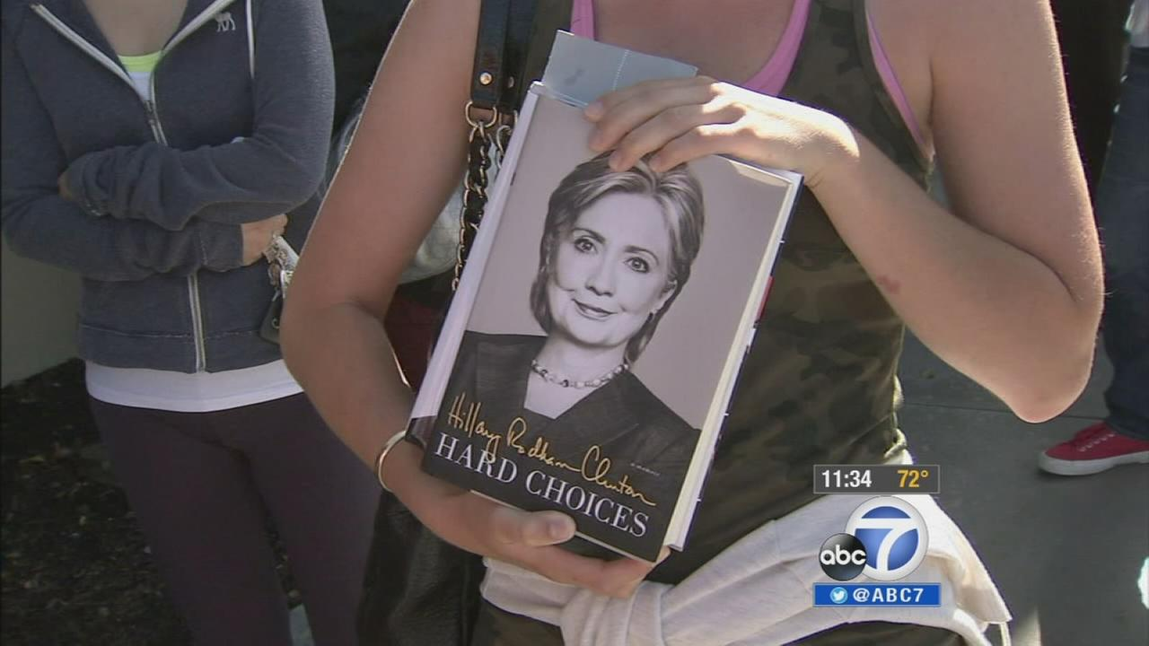 A woman holds up her copy of Hard Choices by Hillary Clinton as she waits in line at a book signing at The Grove on Thursday, June 19, 2014.