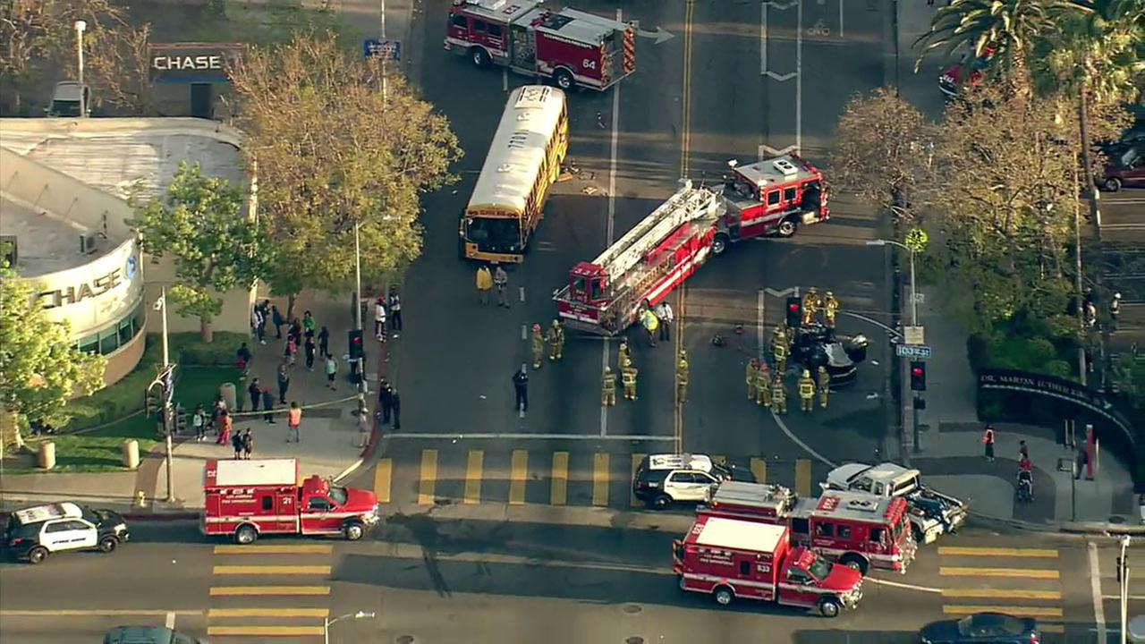 Fire department personnel work the scene of a crash involving a car and a school bus in Watts on Thursday, March 17, 2016.
