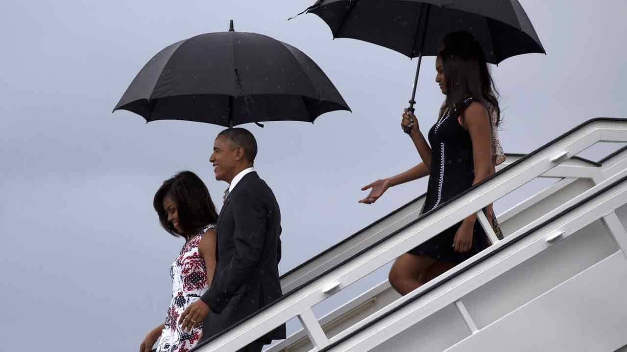 Obama arrives with first lady Michelle Obama, left, and their daughters Sasha, front right, and Malia, as they exit Air Force One at the airport in Havana, Cuba, March 20, 2016.