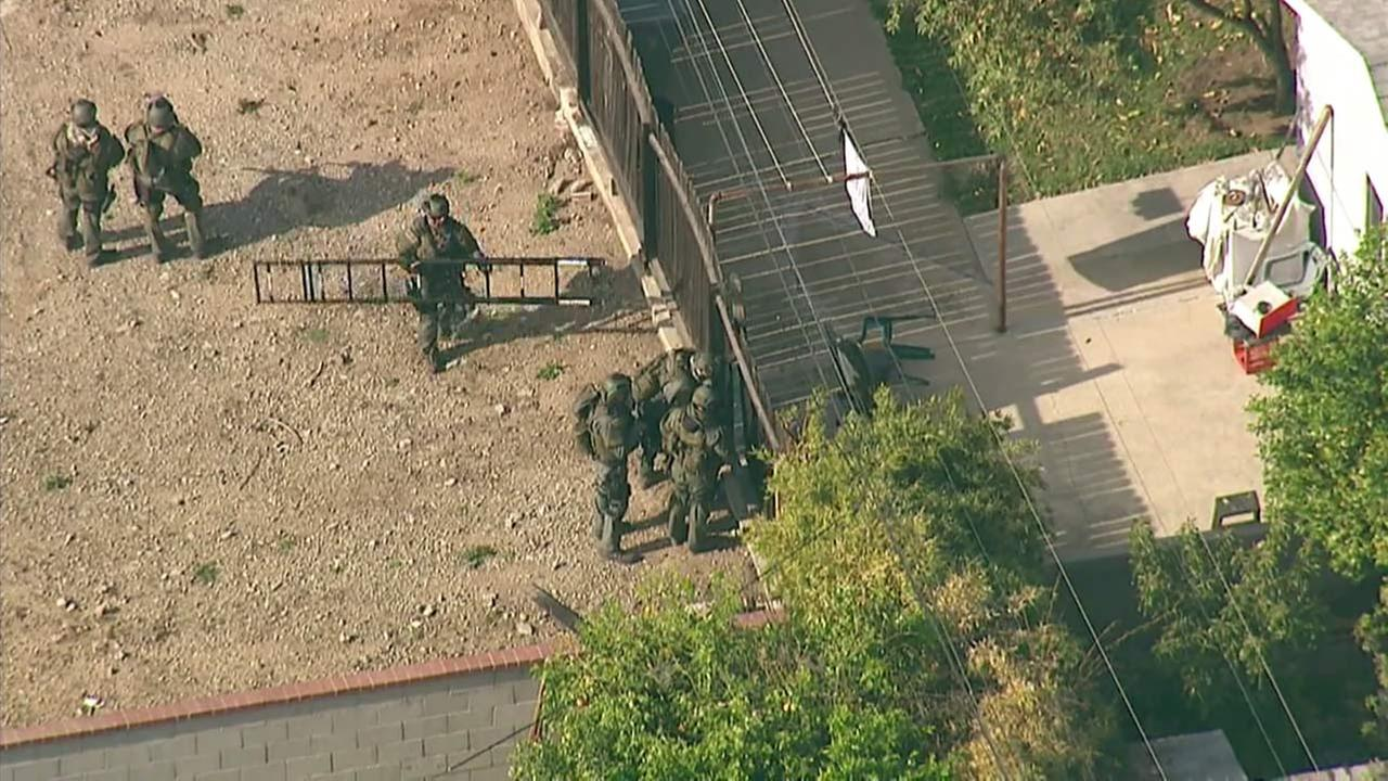 San Bernardino County SWAT team members work to get through a fence in the backyard of a barricaded murder suspect in Chino Hills on Tuesday, March 23, 2016.