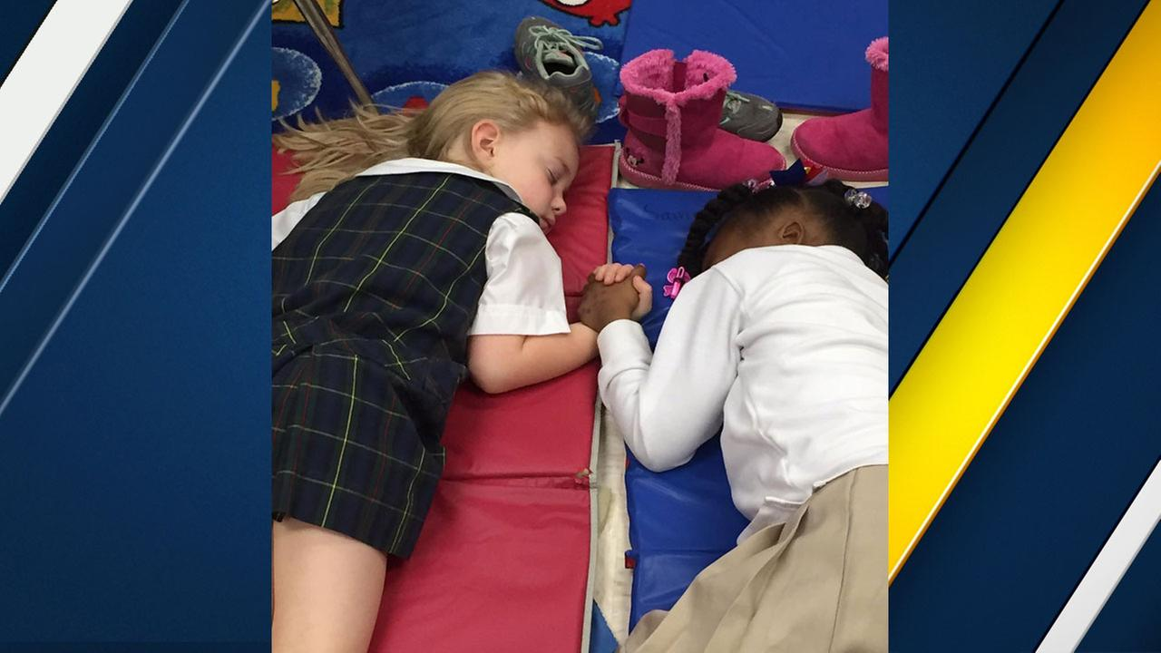 Two little girls are shown sleeping and holding hands in a photo posted by Presbyterian Day School in Clarksdale, Mississippi.