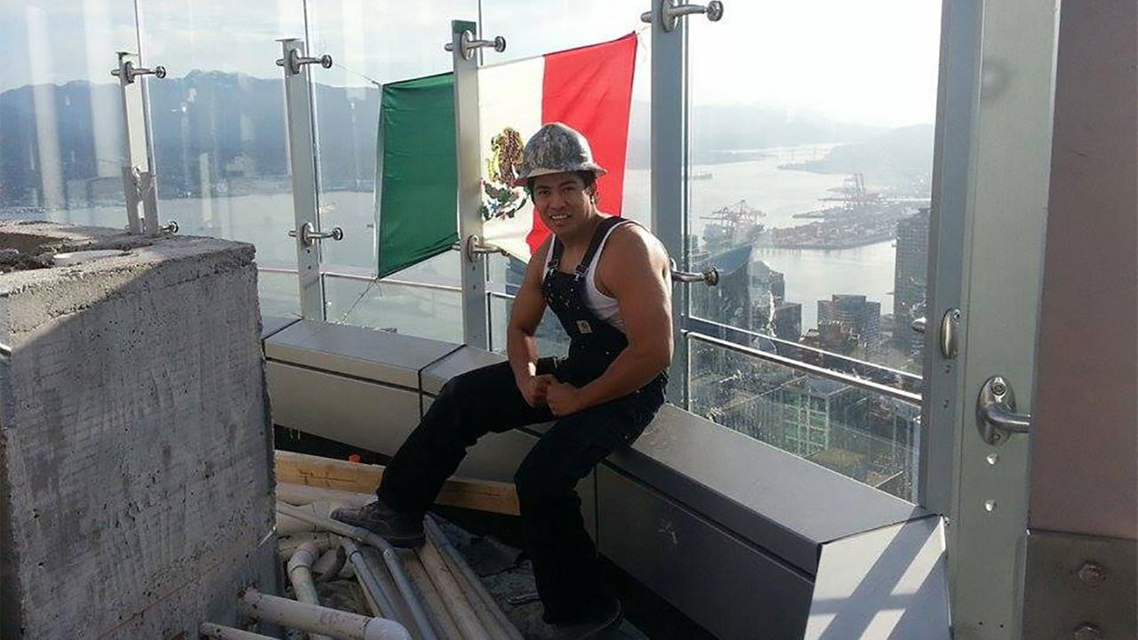 Construction worker Diego Saul Reyna poses alongside a Mexican flag he hung atop the Trump International Hotel in Vancouver.