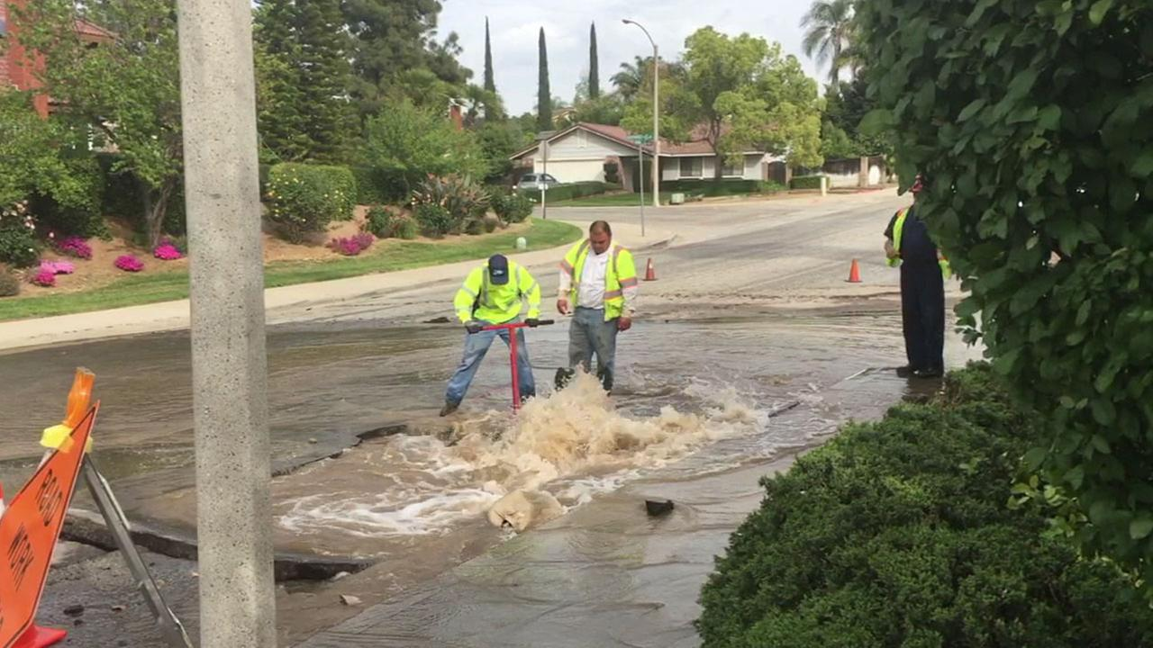 Water district crews work to pump out water from a sinkhole in a Riverside neighborhood after a water main broke on Wednesday, April 6, 2016.