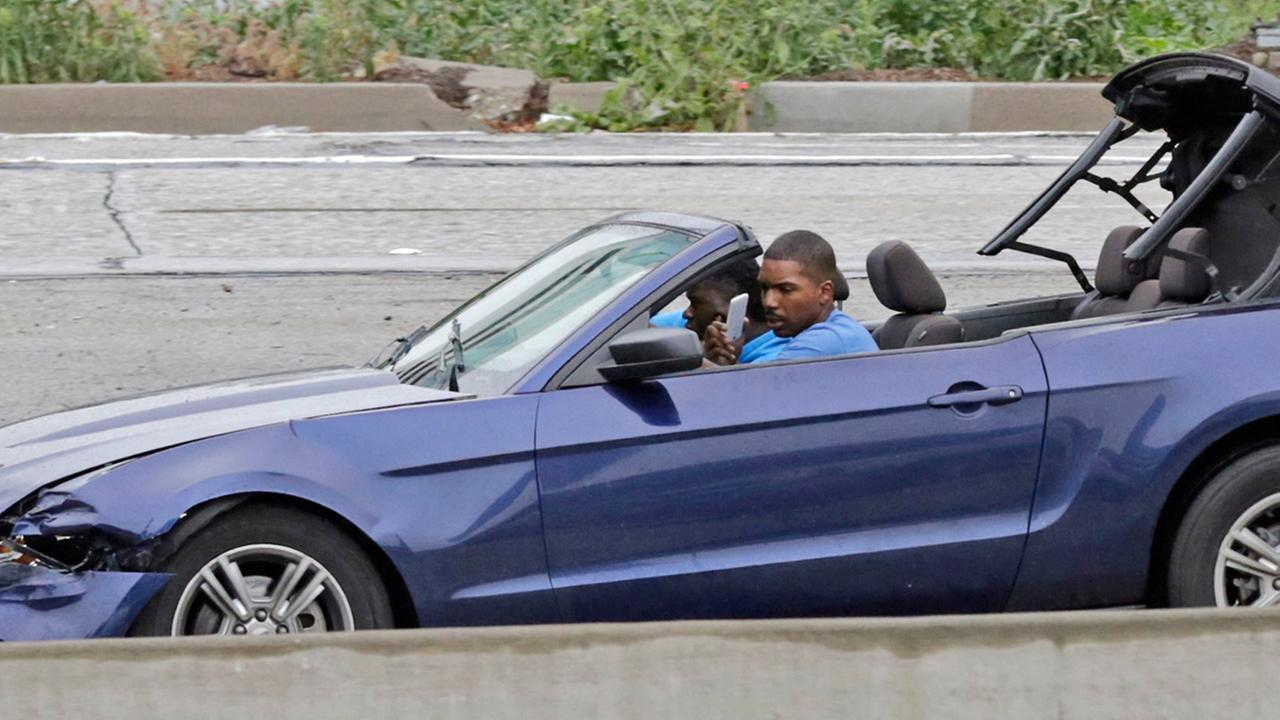 The driver of a convertible blue Mustang holds a personal device and looks into his side-view mirror the busy 110 Freeway during a police chase on Thursday, April 7, 2016.