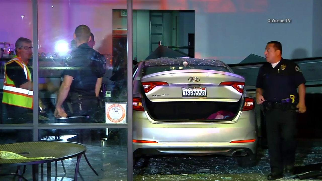 Authorities investigate the scene after a car crashed into an Irvine ice cream shop on Wednesday, April 14, 2016.