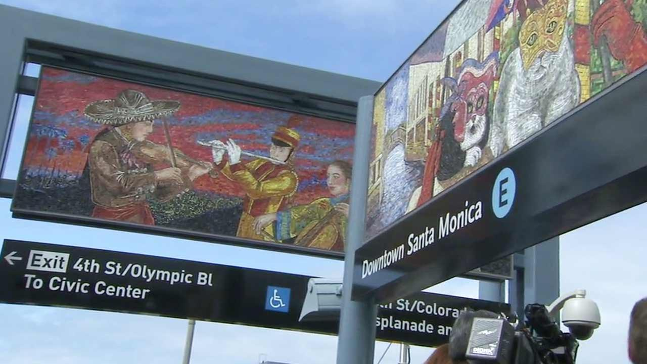 Color murals are shown above Expo Line signs in Santa Monica.