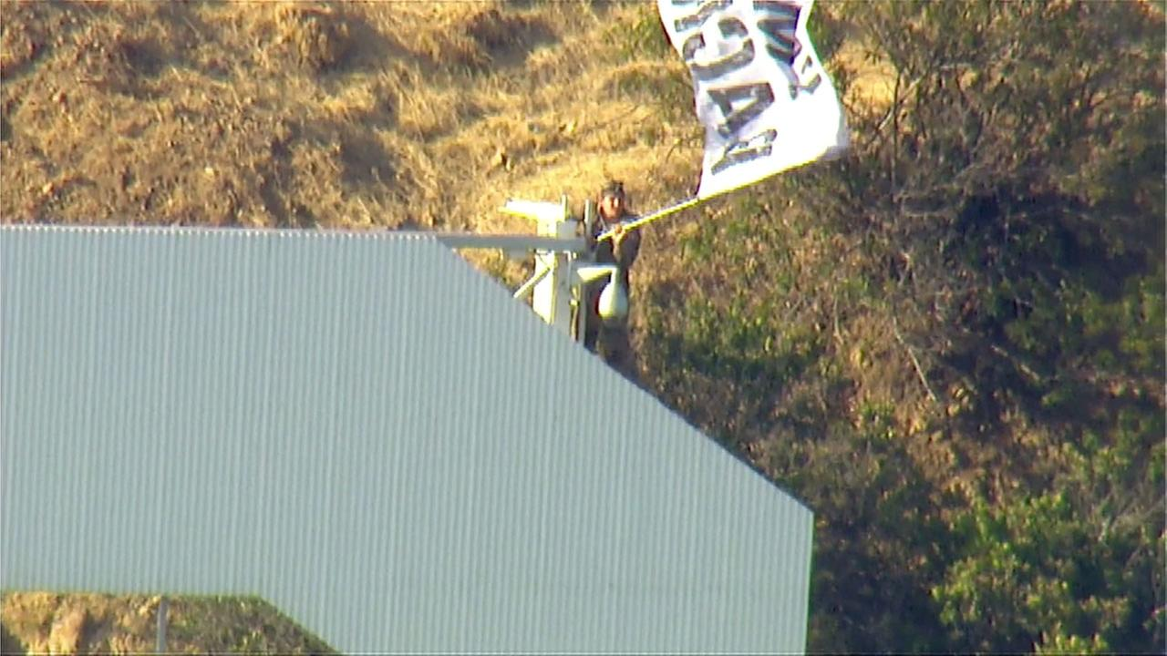 A man climbed the Hollywood sign and waved a banner declaring Im back!