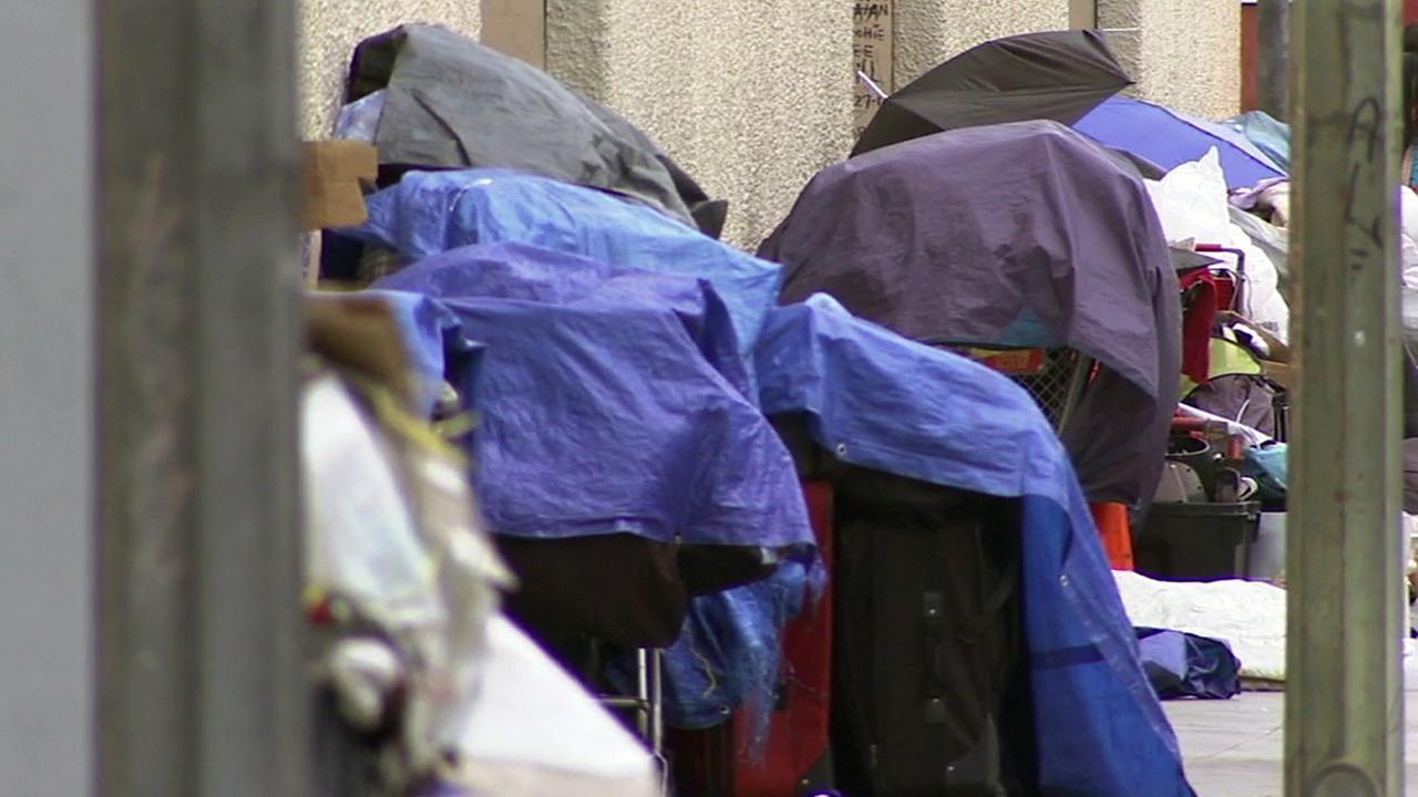 A homeless encampment lines the street.