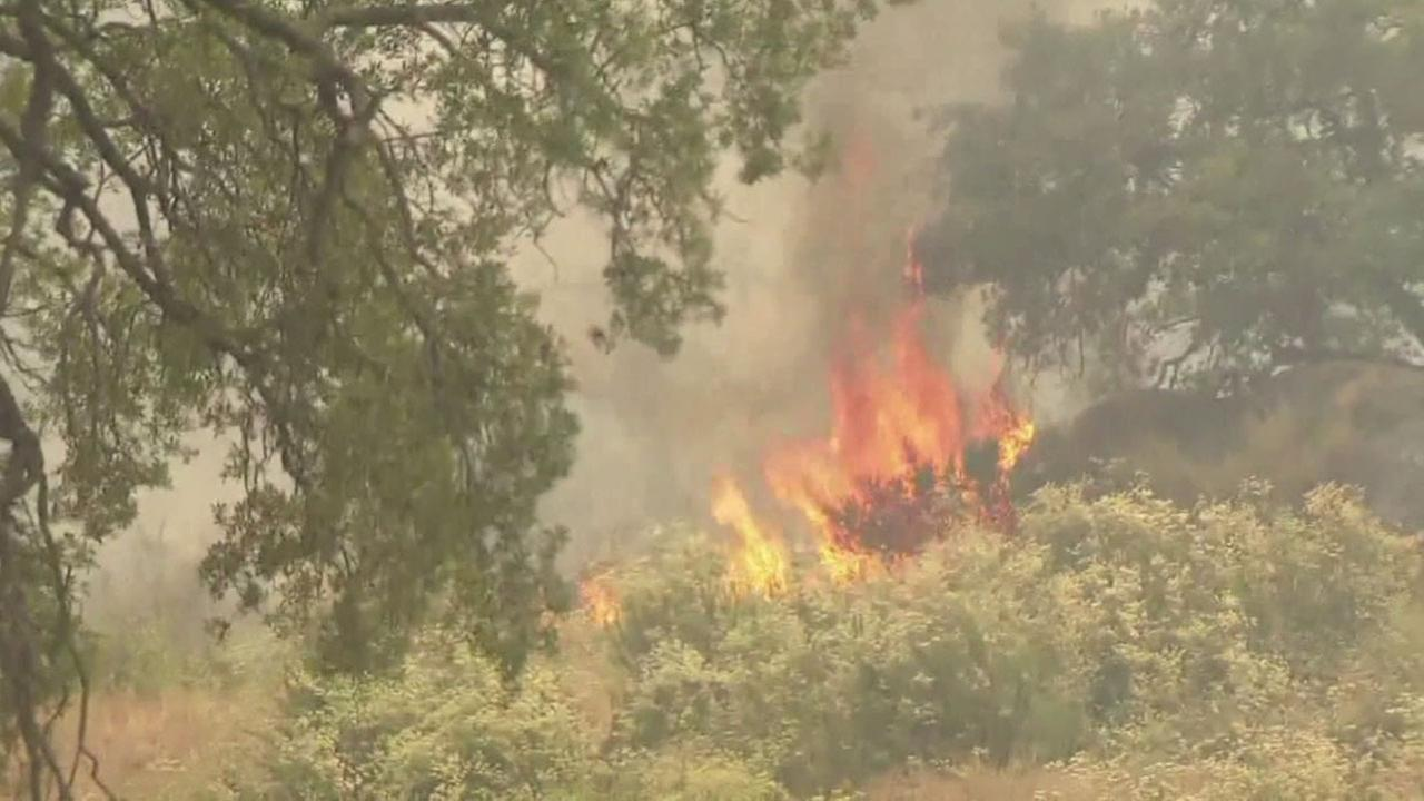 Flames from the Border Fire eat through dry brush in a rural San Diego County community.