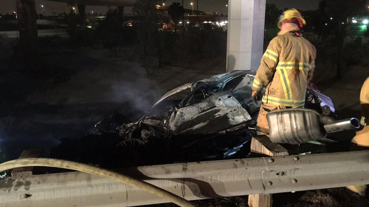 Firefighters work on a smoldering car after the driver crashed it on the southbound 57 Freeway near the 91 Freeway transition on Monday, July 4, 2016.
