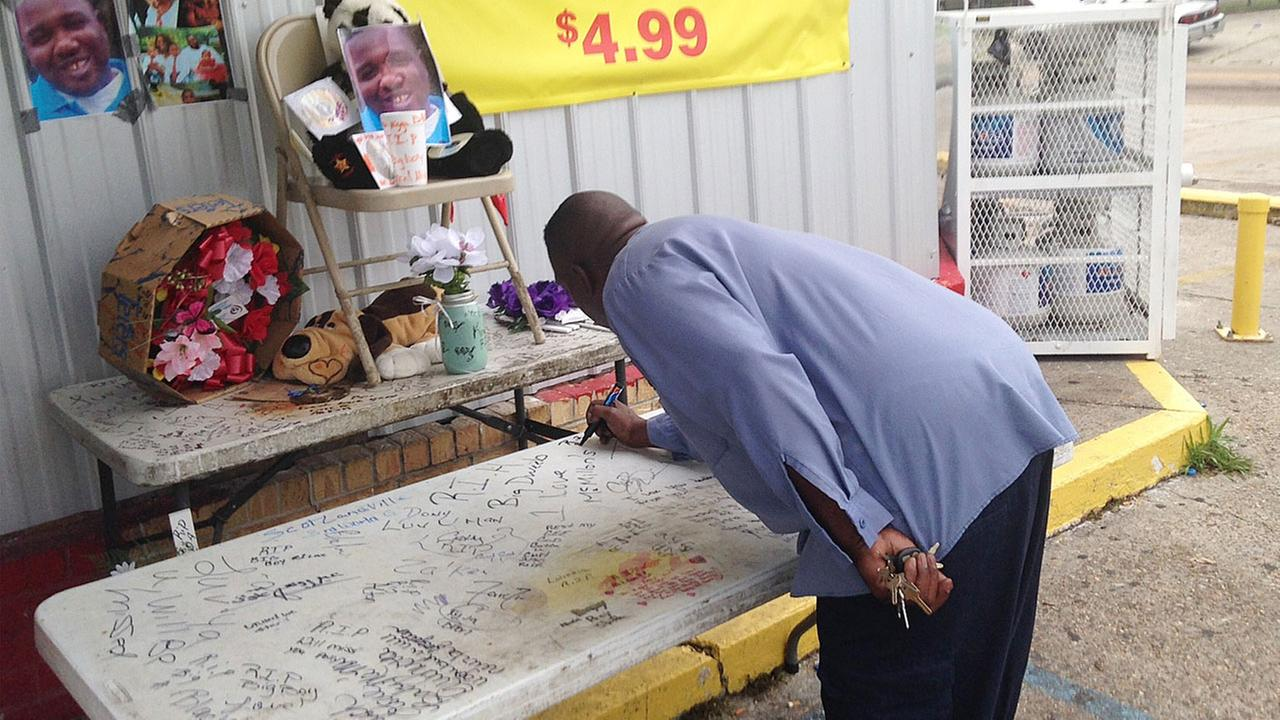 Arthur Baines signs RIP Big Dogg on a folding table that Alton Sterling used to sell homemade CDs outside the convenience store, Wednesday, July 6, 2016, in Baton Rouge, La.