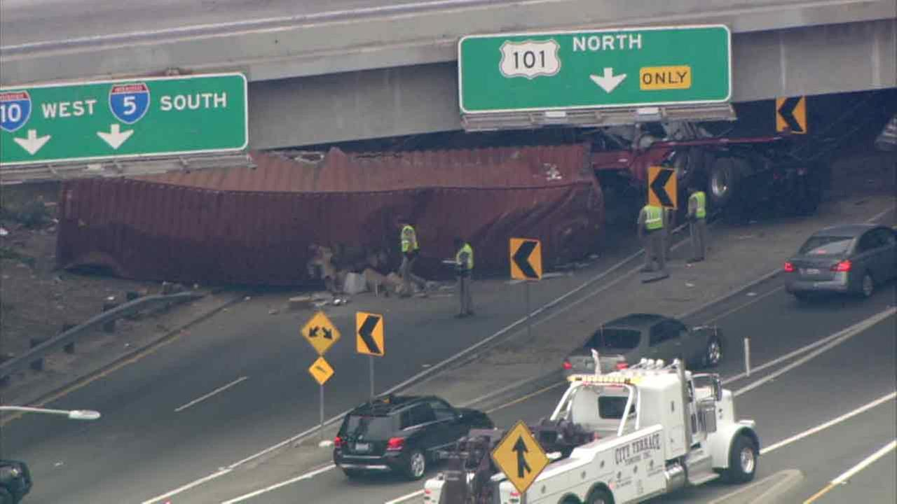 A big rig rolled down an embankment and jackknifed, blocking a freeway transition road in Boyle Heights on Monday, July 11, 2016.