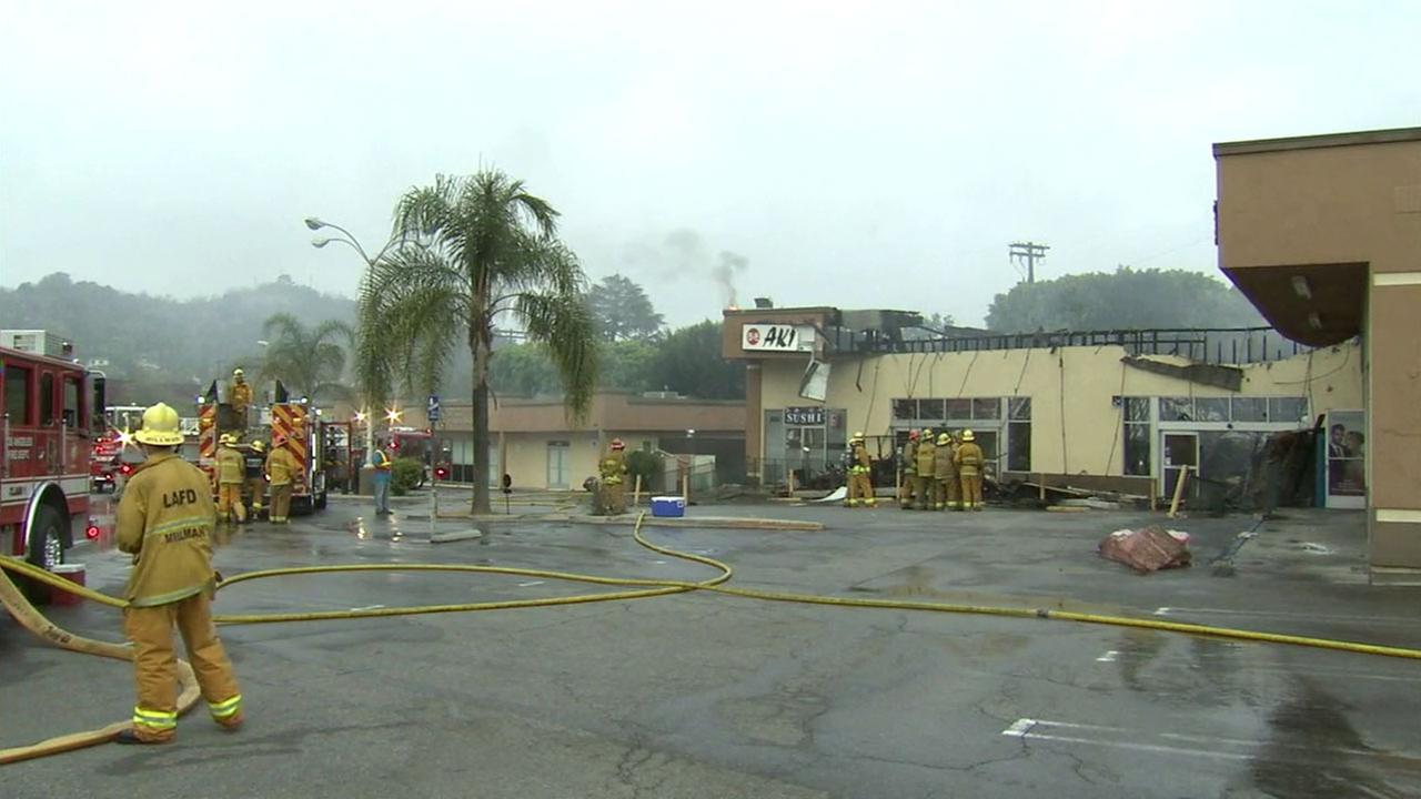 Firefighters survey the damage and put out hot spots after a fire tore through a single-story building in Monterey Hills on Wednesday, July 13, 2016.