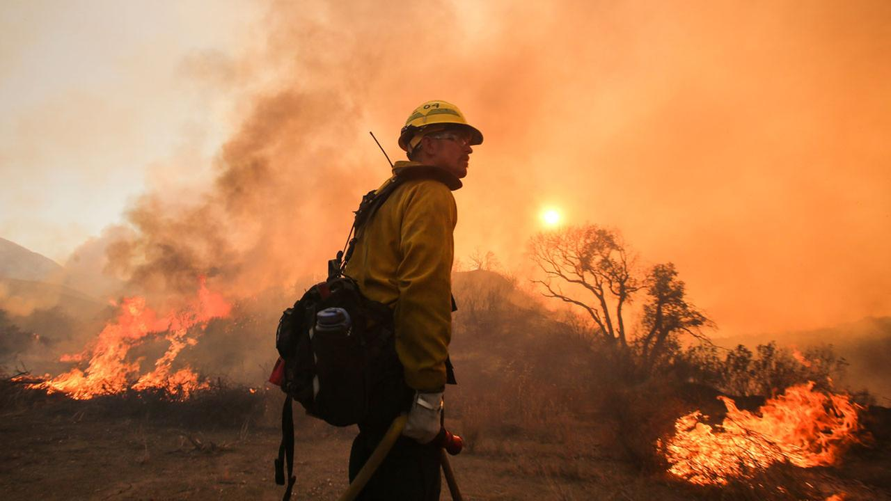 A firefighter watches a wildfire near Placenta Caynon Road in Santa Clarita, Calif., Sunday, July 24, 2016.