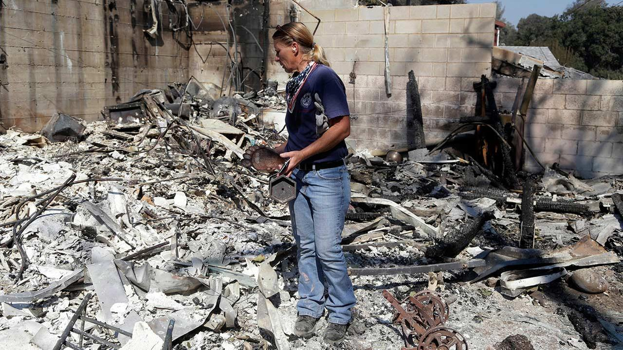 Karrie H. Andrews recovers items salvaged from the ruins of her home Tuesday, July 26, 2016, destroyed when the Sand fire swept through Santa Clarita, Calif. over the weekend.