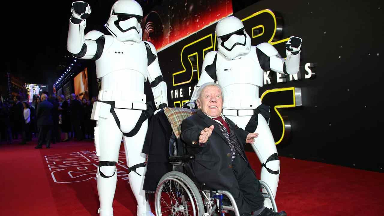 Kenny Baker, center, poses for photographers upon arrival at the European premiere of the film Star Wars: The Force Awakens  in London, Wednesday, Dec. 16, 2015.