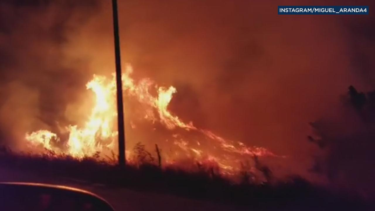 A passing motorist caught the intense flames of a brush fire the erupted along the northbound 15 Freeway near Devore on Saturday, Sept. 3, 2016.