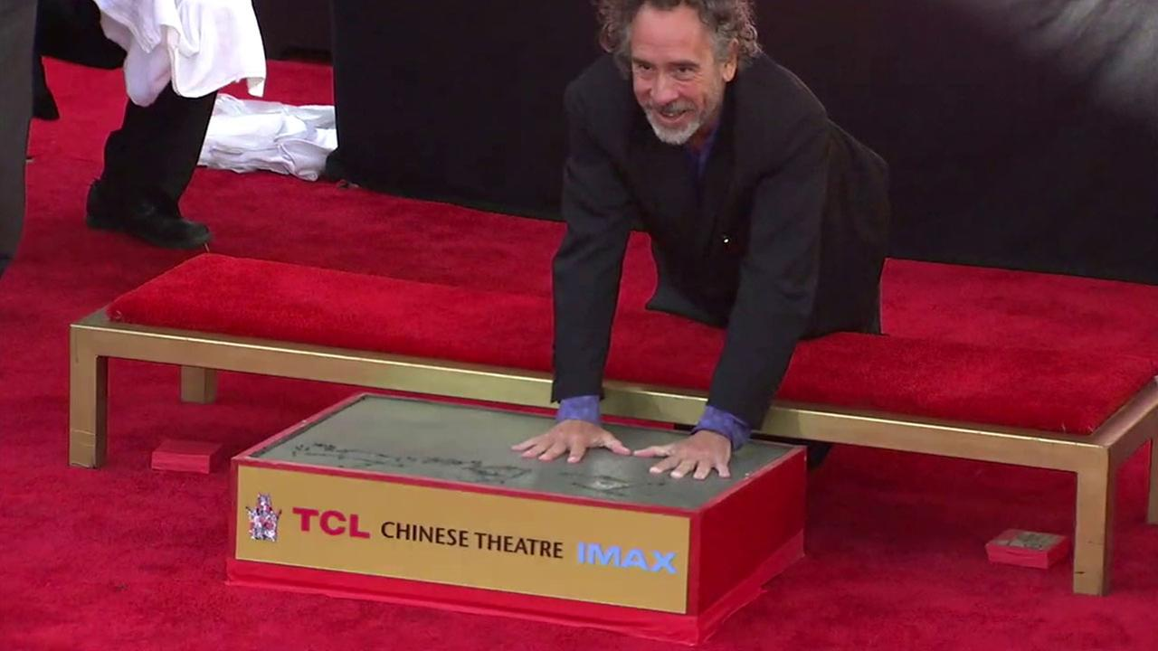 Director Tim Burton puts his hands in cement after signing his name across the top during his handprint ceremony outside of the TCL Chinese Theatre on Thursday, Sept. 8, 2016.
