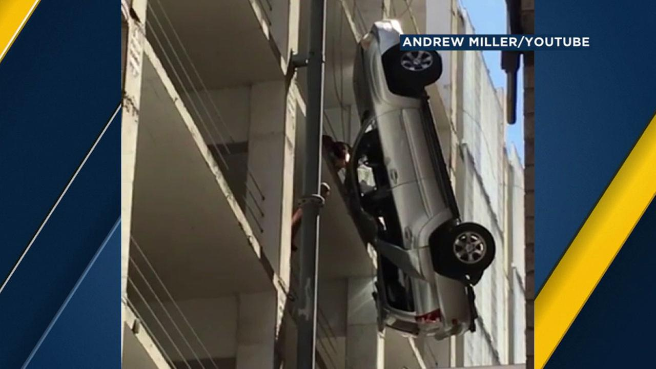 A man climbs out of his car after it flipped over the side of a parking garage in Austin, Texas on Friday, Sept. 9, 2016.