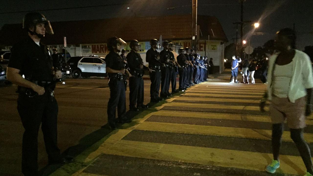 LAPD officers in riot gear formed a line at a South Los Angeles intersection Sunday, Oct. 2, 2016, after protests erupted over a fatal police shooting the previous day.