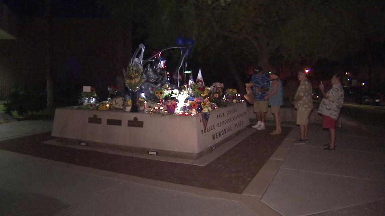 Palm Springs residents brought flowers and other items at a growing memorial in front of the police station on Saturday, Oct. 8, 2016.