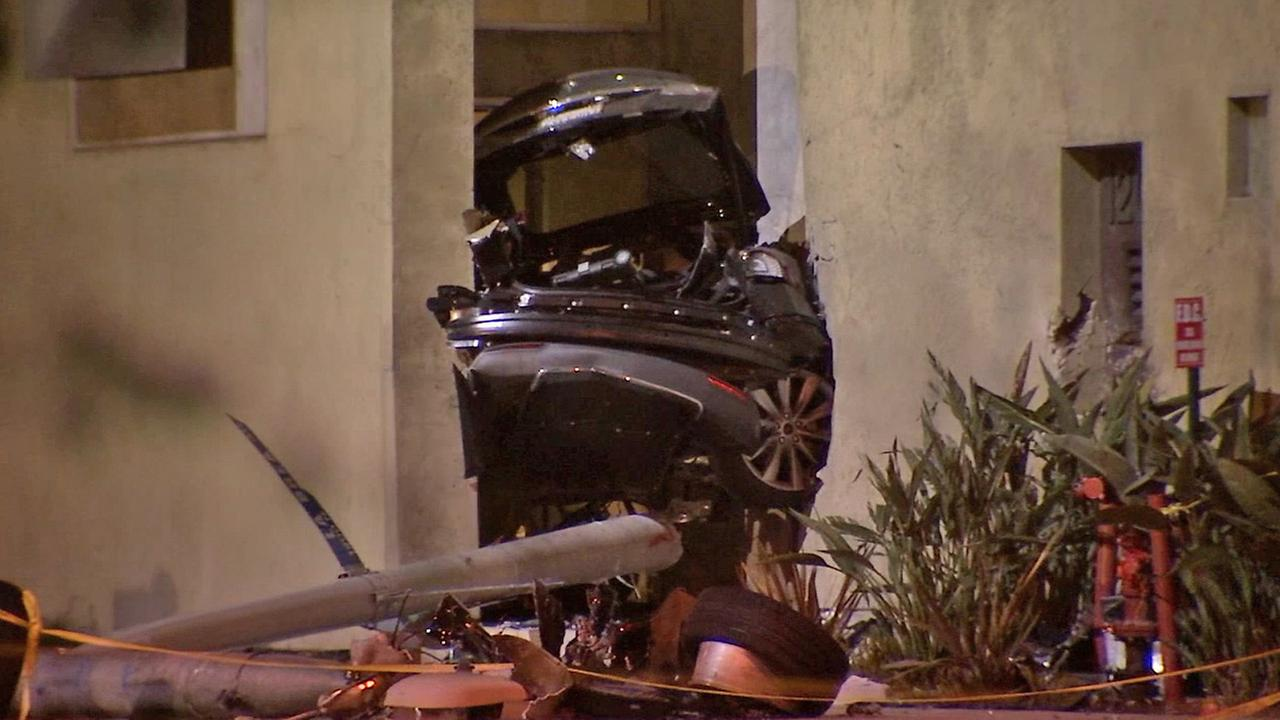 Half of a Tesla is seen wedged between two buildings in West Hollywood on Friday, July 4, 2014.