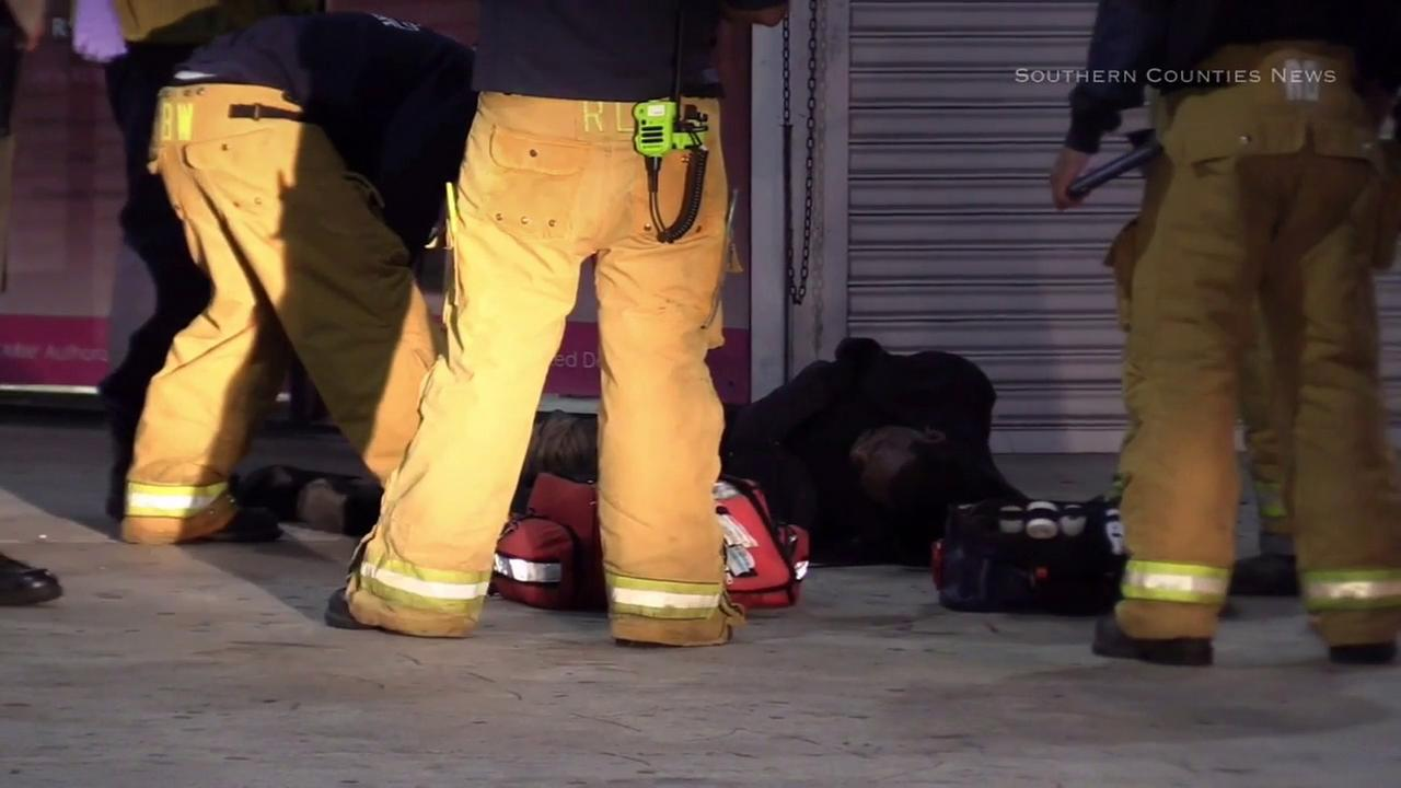 A man is attended by Los Angeles County firefighter-paramedics after he fell from the roof of a commercial building in Compton on Wednesday, Oct. 19, 2016.