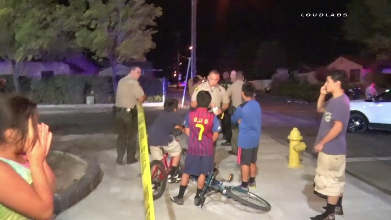 A San Bernardino County sheriffs deputy speaks with a group of boys at the scene of a hit-and-run crash in Victorville on Thursday, Oct. 20, 2016.