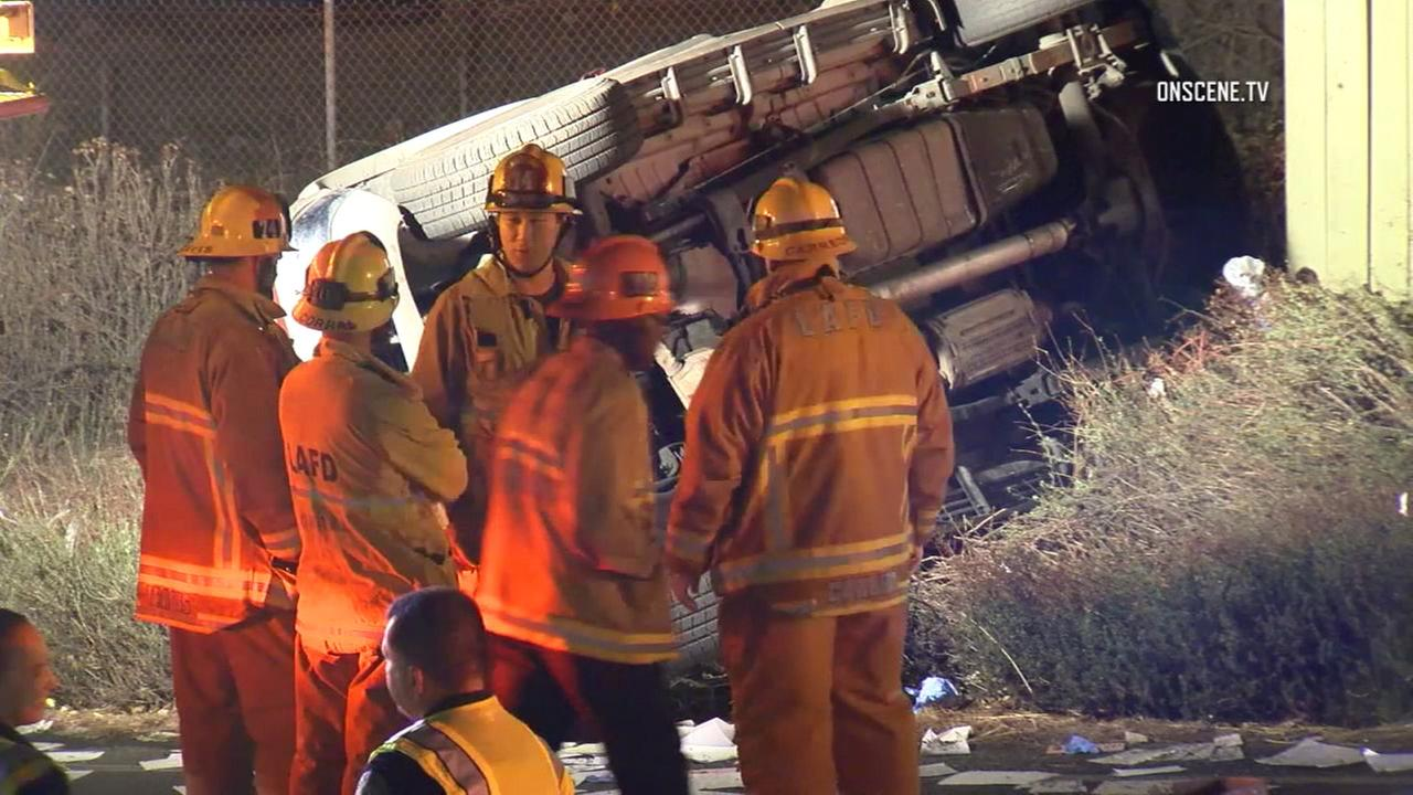 Los Angeles firefighters are seen at the site of a fatal rollover crash in Tujunga on Thursday, Oct. 27, 2016.