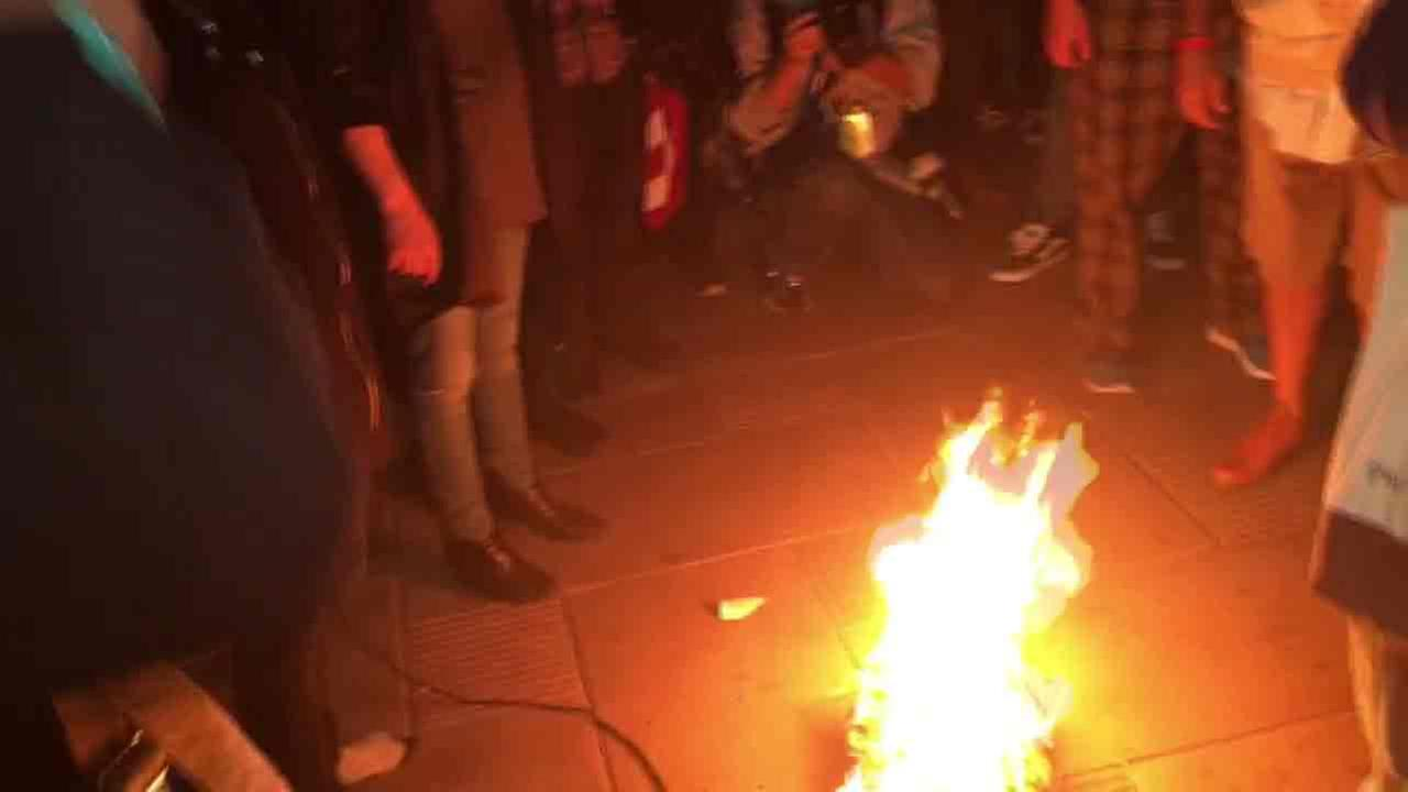 Anti-Trump protesters burn an American flag after the billionaire businessman is declared the new president-elect.