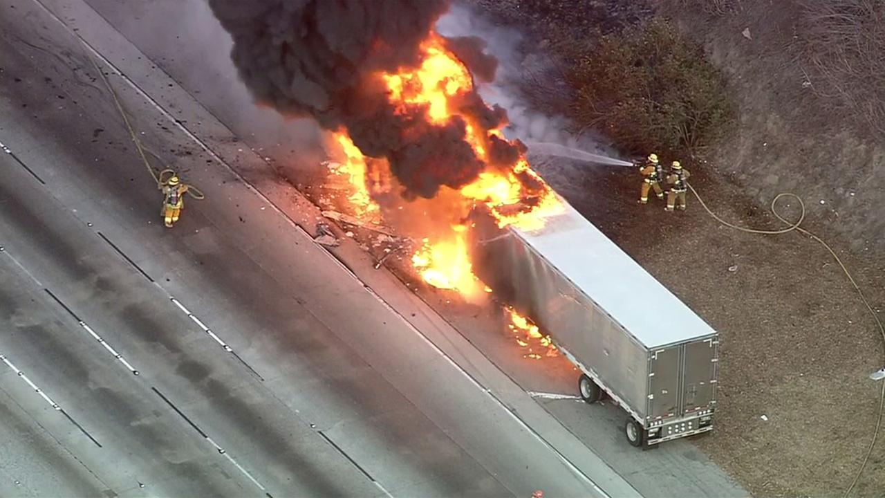 Firefighters worked to put out a semi-truck fire after it burst into flames along the eastbound 60 Freeway in the City of Industry on Thursday, Nov. 10, 2016.