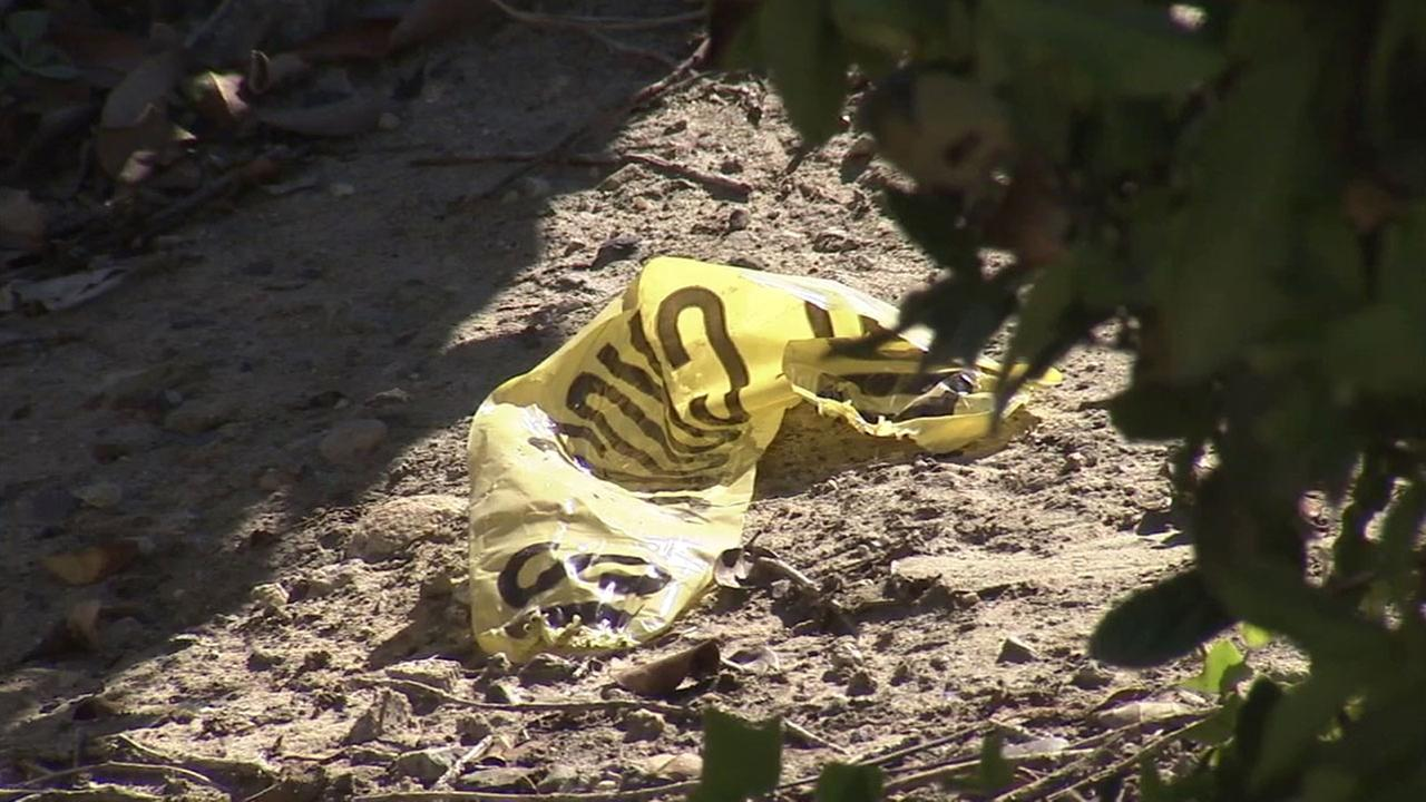 A piece of police crime tape sits in the area where a womans body was found behind a bank in Mission Viejo.