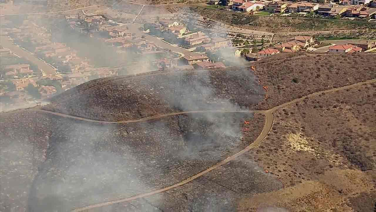 A brush fire is seen approaching a San Juan Capistrano neighborhood on Sunday, Nov. 13, 2016.