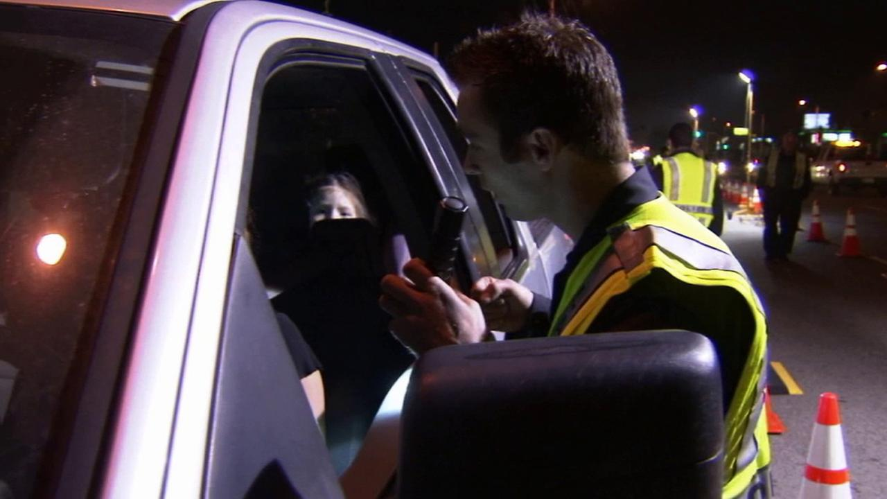 An officer stops a car during a DUI check in this undated file photo.