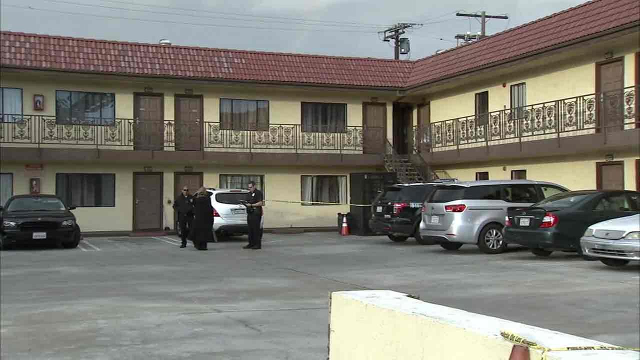 Authorities investigate the scene where a woman was found beaten to death inside a motel room on Sunday, Nov. 27, 2016.
