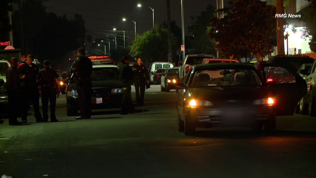 Los Angeles Police Department officers are stand near a car that was shot at early Friday, Dec. 9, 2016, in an incident that left a teenager critically wounded.