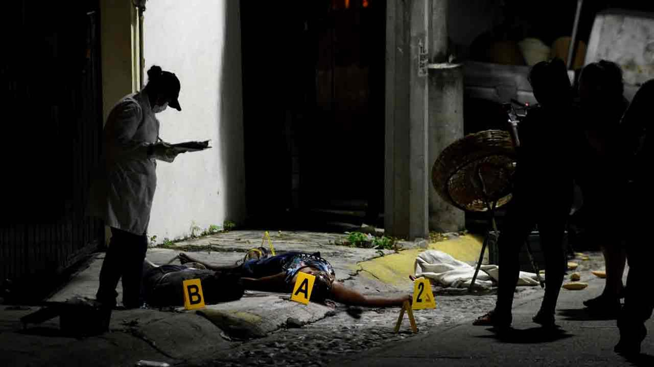 A forensic medic investigates the crime scene where two people were shot dead by unidentified attackers in Acapulco, Mexico, Thursday, Dec. 8, 2016.