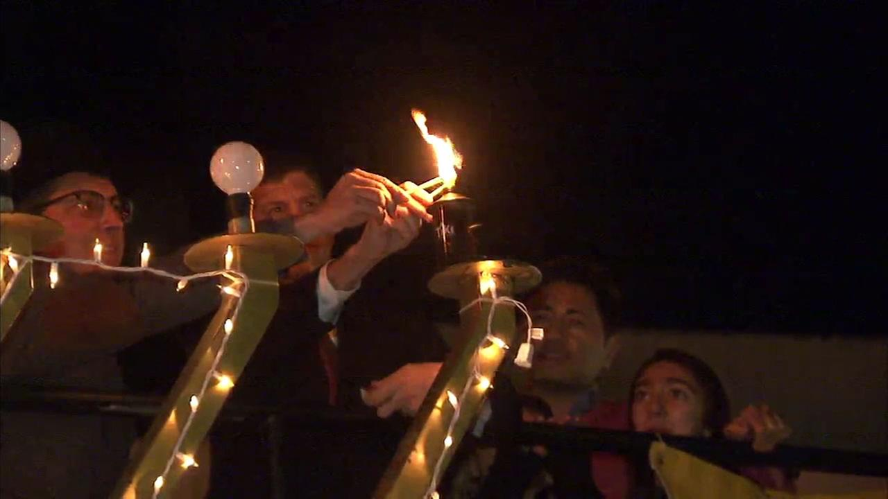 Southern California residents light a menorah in Beverly Hills for the first night of Hanukkah Christmas Eve, Dec. 24, 2016.