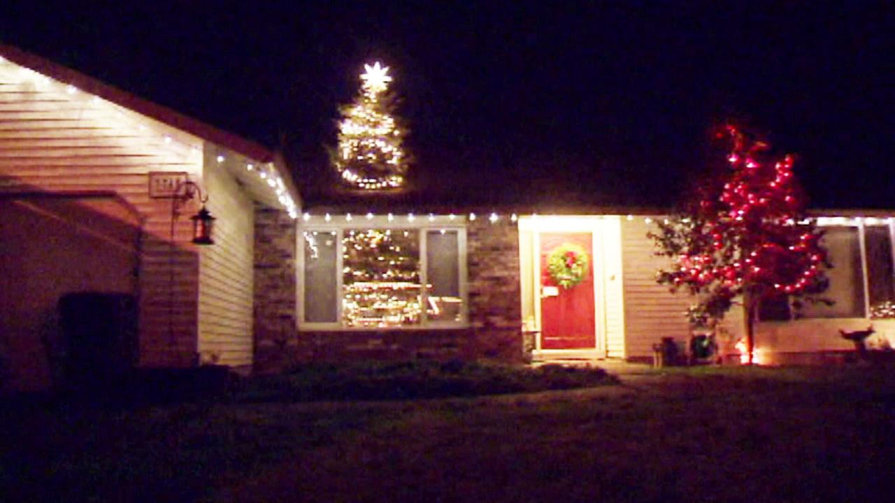 A 20-foot Christmas tree, put together by a father and son in Oregon, appears to poke through their one-story home on Christmas Eve, Dec. 24, 2016.