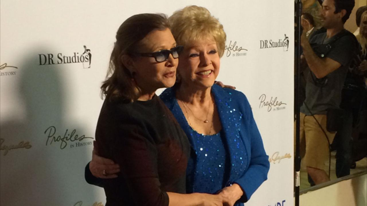 Carrie Fisher and mother Debbie Reynolds pose for cameras in an undated photo.