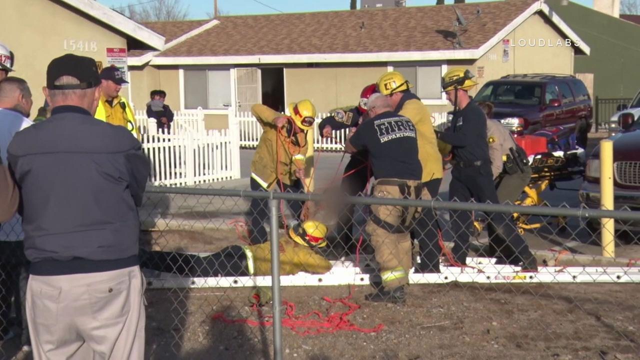 San Bernardino County firefighters rescue a boy who fell down a 15-foot sinkhole in Victorville on Sunday, Jan. 15, 2017.