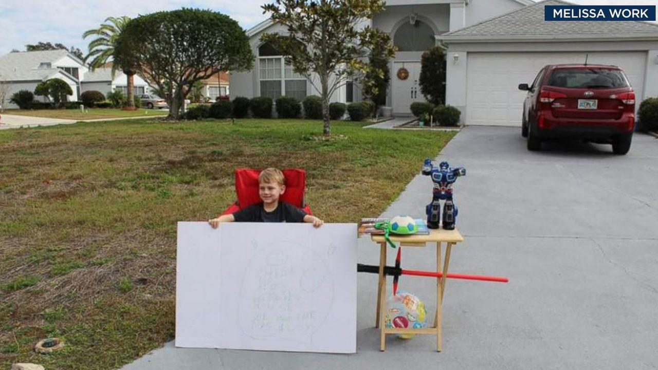 Blake Work, 6, is shown holding his sign in front of his free toy stand at his Florida home.