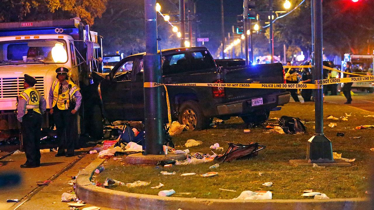 Police stand next to a pickup truck that slammed into a crowd and other vehicles, causing multiple injuries at a Mardi Gras parade in New Orleans on Saturday, Feb. 25, 2017.